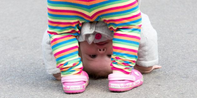 TORONTO, ONTARIO, CANADA - 2014/09/20: Cute child looking through her legs with the head close to the...