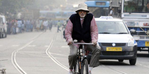 KOLKATA, INDIA - NOVEMBER 6: Bollywood actor Amitabh Bachchan rides a bicycle during shooting for his...