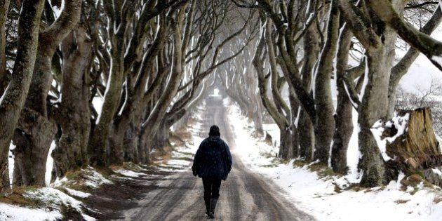 A man walks during snow along the Dark Hedges tree tunnel, which was featured in the TV series Game of...