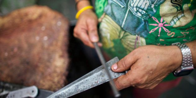 A butcher sharpens a knife before cutting buffalo meat, unseen, at a beef store in New Delhi, India,...