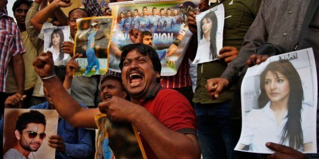 Indian fans shout slogans with posters of Indian cricket player Virat Kohli, left and his girlfriend...