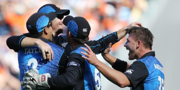 New Zealand's Martin Guptill, second left, is congratulated by teammates after taking a catch to dismiss...