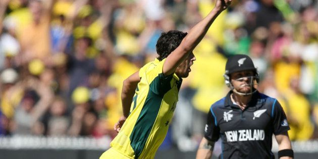 Australia's Mitchell Starc, left, celebrates after taking the wicket of New Zealand captain Brendon McCullum...