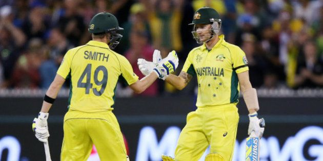Australian captain Michael Clarke, right, is congratulated by teammate Steve Smith after scoring 50 runs...