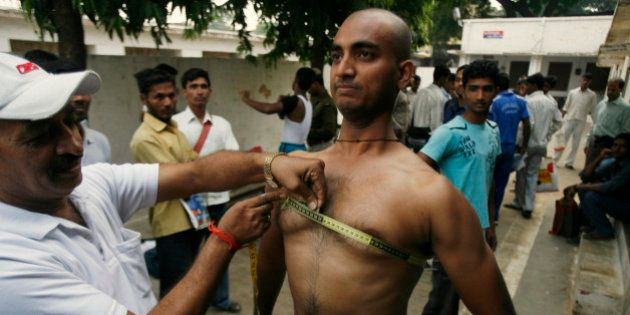 A candidate gets his chest measured as part of a fitness test during recruitment for Uttar Pradesh state...