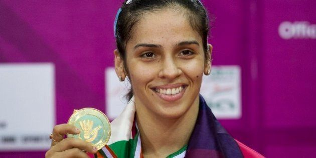 India's Saina Nehwal displays her gold medal after defeating Thailand's Ratchanok Intanon in the women's...