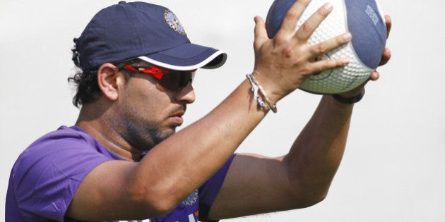 India's Yuvraj Singh holds a ball during a practice session in Ahmadabad, India, Tueday, Nov. 13, 2012....