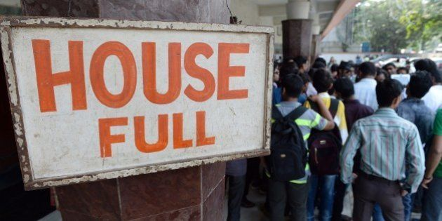 Disappointed moviegoers are seen next to a board announcing 'full house' for a screening of the popular...