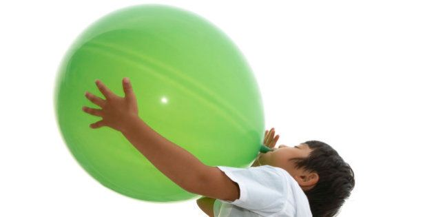 boy blowing up a big green
