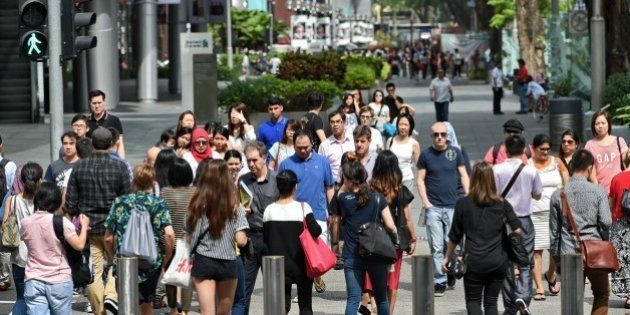 Pedestrians cross a street at the Orchard Road shopping district in Singapore on March 12, 2015. AFP...