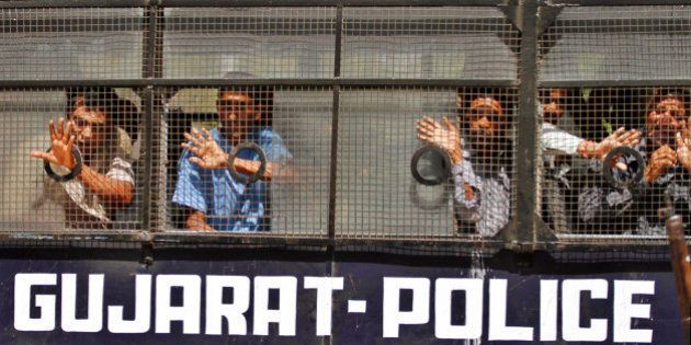 Convicted Indians wave to their families from inside a police vehicle as they are taken away after the...