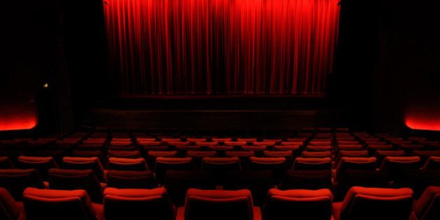 Darkened, empty cinema auditorium with red curtain covering screen, and red