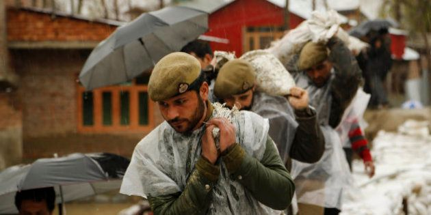 Jammu and Kashmir policemen carry sand bags to repair a breach in an embankment in a flooded area of...