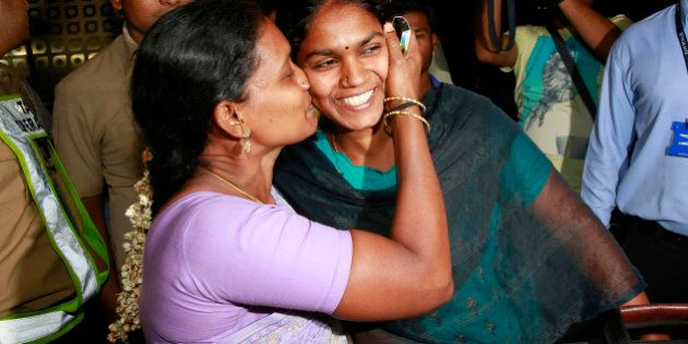 An Indian woman, left, greets her relative who arrived at Chhatrapati Shivaji International Airport in...