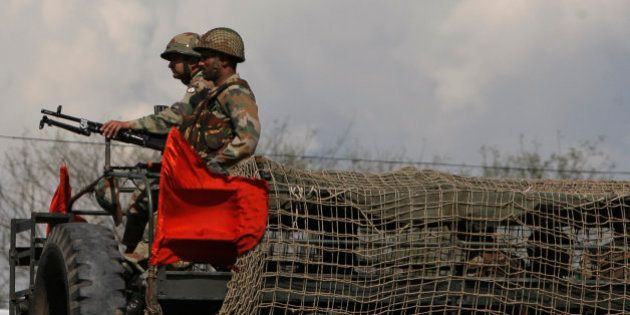 Indian army soldiers take position on a truck during an attack by suspected Kashmiri rebels near an army...