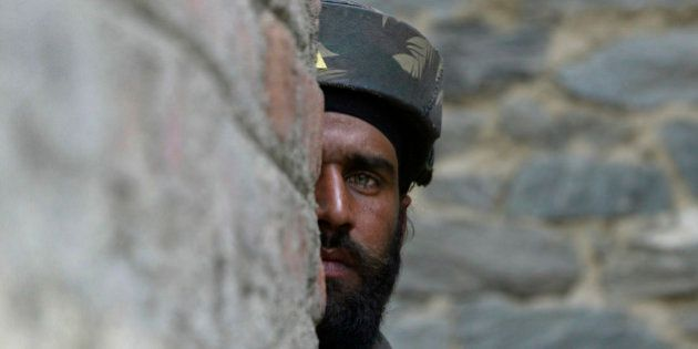 An Indian Army soldier looks on during a gun battle in Baramulla, about 55 kilometers (34 miles) north...