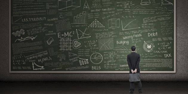 Businessman is looking at a huge hand drawn chalkboard in a