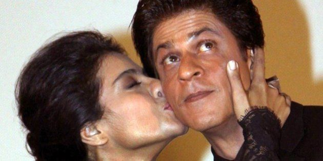 Indian Bollywood film actors Shah Rukh Khan (R) and Kajol Devgan pose during the celebration of the successful...