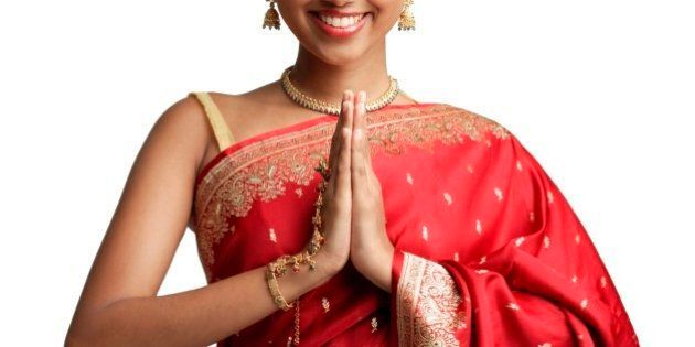 Woman in traditional Indian costume, standing with hands together, smiling at
