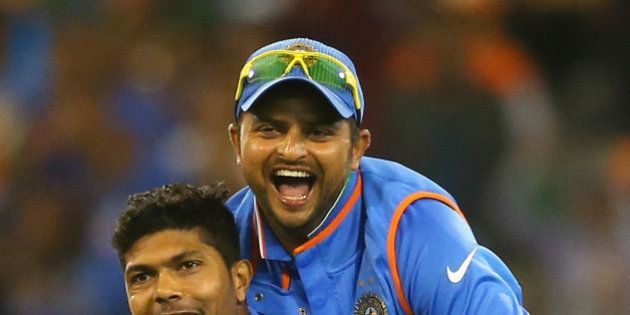 MELBOURNE, AUSTRALIA - MARCH 19: Umesh Yadav of India is congratulated by Suresh Raina after getting...
