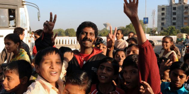 Indian mountaineer Malli Mastan Babu (C) poses with children in Ahmedabad on November 29, 2009, following...