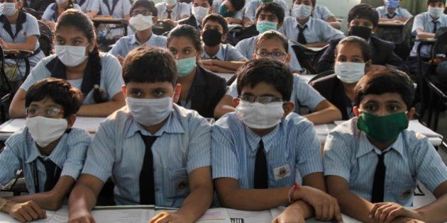 Indian students wear masks for protection against swine flu, as they attend their class at a school in...