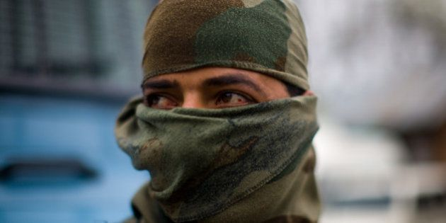 HAURD SHOORA, KASHMIR, INDIA - APRIL 02: An Indian policeman looks toward the gunbattle site where suspected...