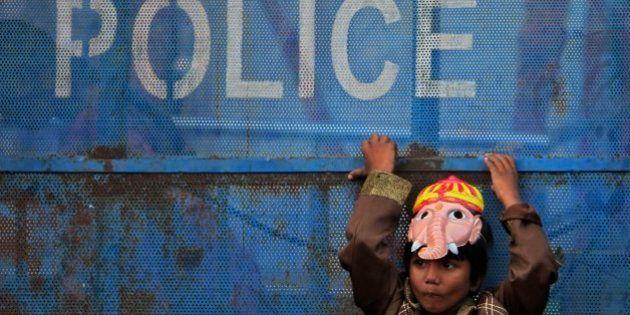 An Indian boy wearing a mask of elephant-headed Hindu god Ganesha leans against a police barricade and...