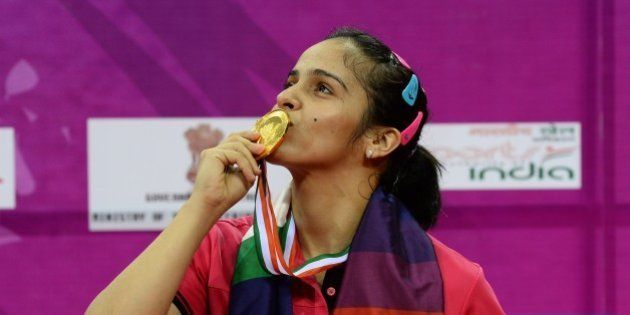 Saina Nehwal of India kisses her gold medal after winning her women's singles final match against Ratchanok...