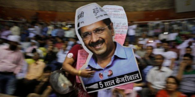 A supporter carries cut-outs of Delhi Chief Minister Arvind Kejriwal during a ceremony to launch an anti-corruption...