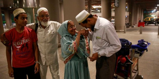 An Indian Muslim man greets his mother after she arrived at Chhatrapati Shivaji International Airport...