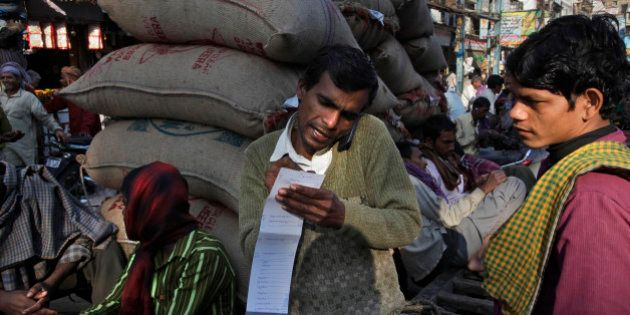 A vendor takes an order from a customer on his mobile phone at a wholesale market, in New Delhi, India,...