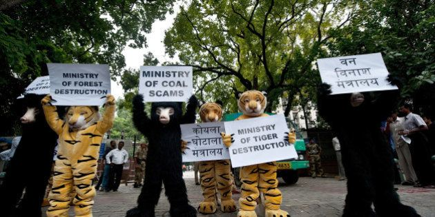 Greenpeace activists dressed as bears and tigers hold placards during a protest, urging the government...