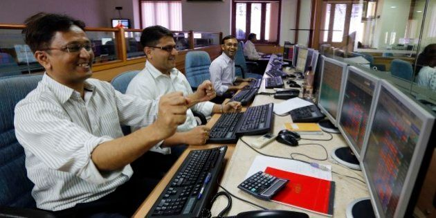 Indian stockbrokers celebrate as they watch the Bombay Stock Exchange (BSE) index on their trading terminal...