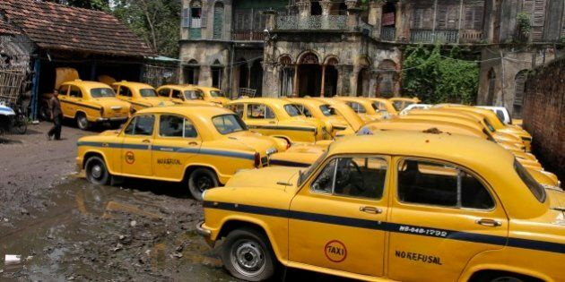 Ambassador cars, converted to yellow cabs are parked in front of a century old building during a daylong...