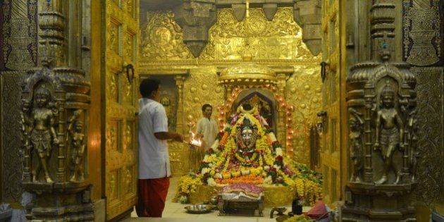 Indian Hindu priests perform the 'Aarti' religious ritual at the Somnath temple, recently decorated by...