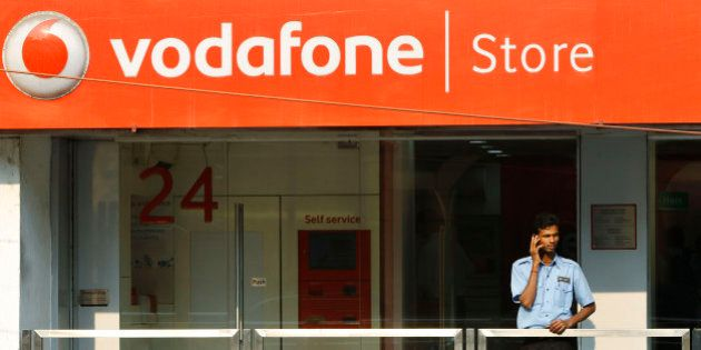 A security guard talks on his mobile phone outside a Vodafone store in Bangalore, India, Friday, Jan....