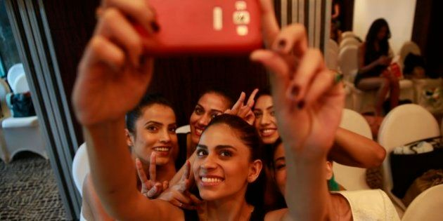 An Indian model takes a photograph of herself with other models on a mobile phone as they wait to participate...