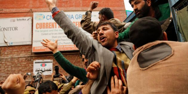 In this Wednesday, April 8, 2015 photo, Kashmiri government teacher shout slogans after being detained...