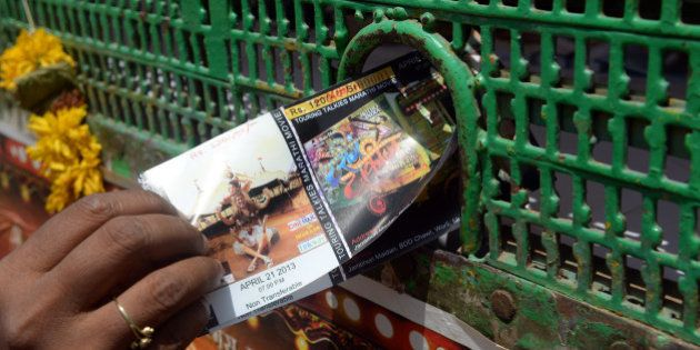 A cinema-goer collects her ticket from a counter outside the premises of the Anup Touring Talkies tent...