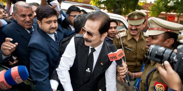 Security officials escort India's Sahara group chairman Subrata Roy (C) on his arrival at the Supreme...
