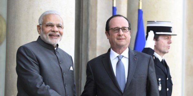 French President Francois Hollande (R) shakes hands with Indian Prime Minister Narendra Modi as he welcomes...