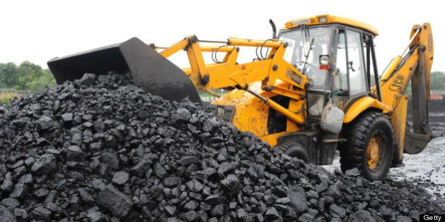 An Indian truck driver prepares to load coal onto a truck at the Kankaria Railway yard in Ahmedabad on...