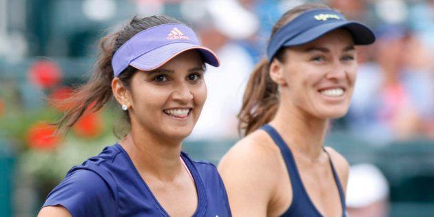 Sania Mirza, left, of India, celebrates with her teammate, Martina Hingis, of Switzerland, after defeating...