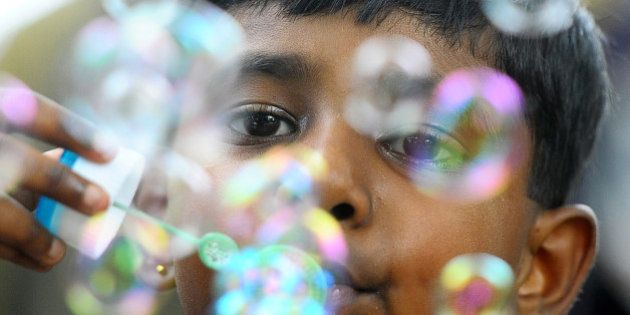 A Sri Lankan child plays with bubbles at the main zoo in Colombo on October 1, 2013. Sri Lanka is marking...