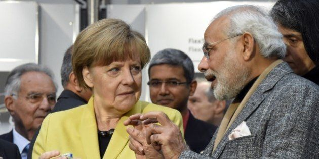 German Chancellor Angela Merkel (L) and Indian Prime Minister Narendra Modi (R) inspect some bionicANTs...