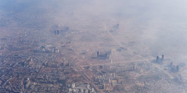 Smog envelops buildings on the outskirts of the Indian capital New Delhi on November 25, 2014. AFP PHOTO/Roberto...