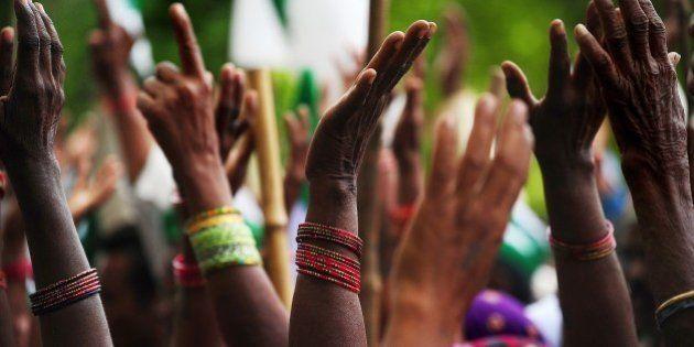 Indian farmers of the Bharatiya Kisan Union (BKU) - Indian Farmers' Union - raise their hands as they...