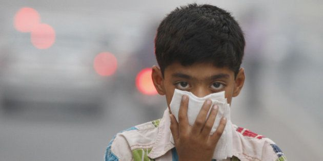 NEW DELHI, INDIA - NOVEMBER 07: A child covers its face to take precaution from the air pollution by...