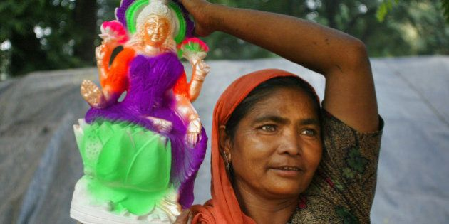 A woman carries an idol of Hindu Goddess Lakshmi for sale in Allahabad, India, Sunday, Oct. 15, 2006....